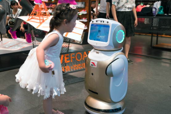 Girl talking to robot in store